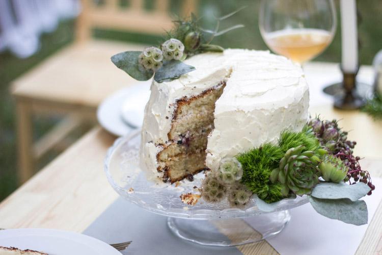 Вкусный праздничный дрезденский торт с изюмом и сливочным сыром и фужер с вином на столе