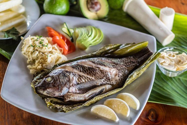 Запеченная в листьях речная рыбка шигли с овощами